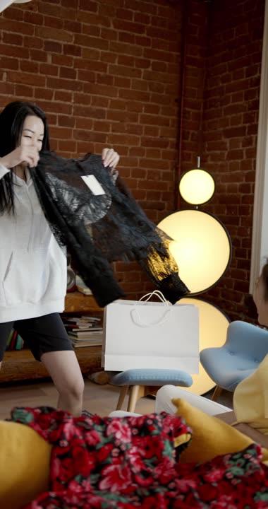 女人帮凯西的服装_一个女人在检查购物袋里买的衣服-视频素材-制片帮